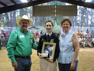 Shelby McClelland accepts a master showmanship award from Tom Browning, a member of the Nevada County Fairgrounds Board of Directors, and Wanda Mertens